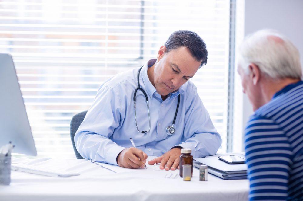 Doctor prescribing medicine to senior patient in clinic